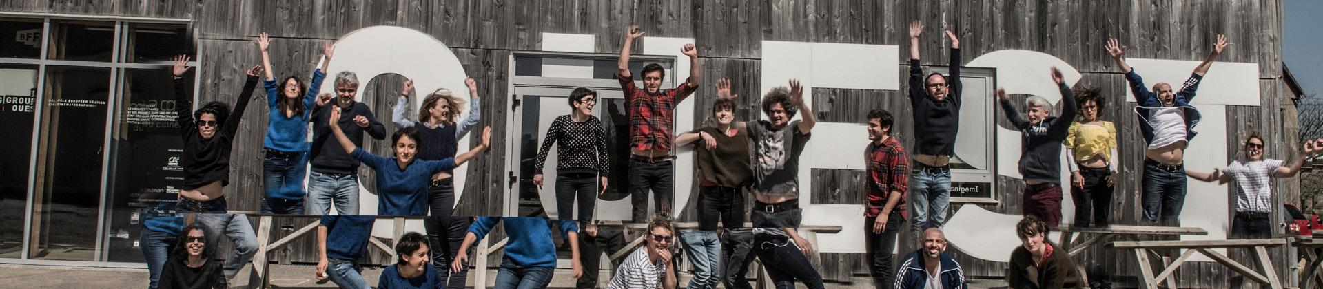 Photo joyeuse d'un groupe d'auteurs sautant devant le Groupe Ouest